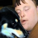 Boy with Down Syndrome hugging a dog